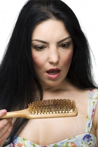 woman looks in shock at her hairbrush