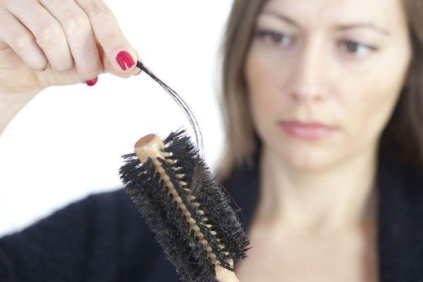 woman looking at hair brush with hair loss